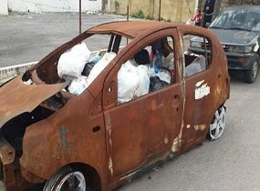 A burnt car turns into trash in Beirut